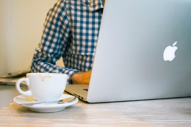 a desk setop with a laptop, cup of coffee and a person who coudl be researching information on a short code