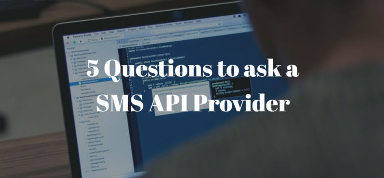 A photo of a programmer writing code on his lapop. there is white text above it that shows the title: 5 Questions to ask a SMS API Provider