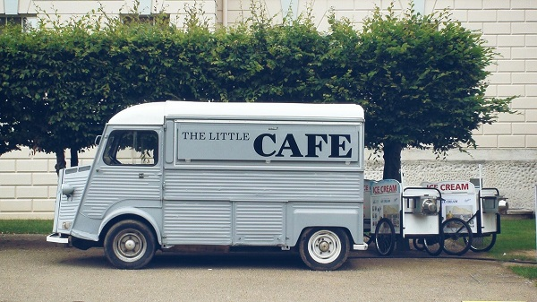 Picture of a grey food truck with ice cream carts behind it
